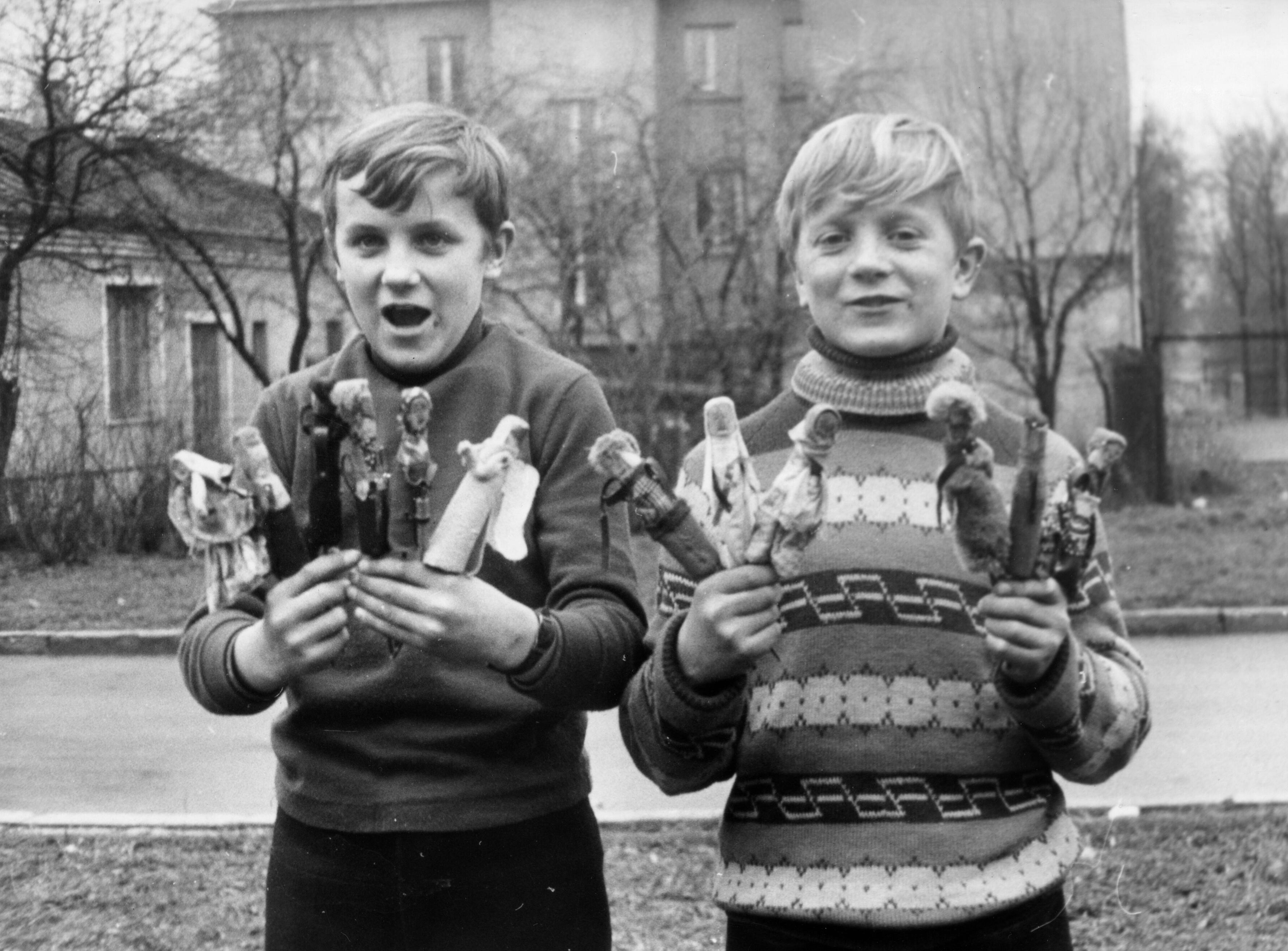 Zdjęcie czarno-białe przedstawiające dwóch chłopców trzymających małe, ręcznie wykonane laleczki kolendnicze. W tle widać ulicę, domy wielorodzinne, drzewa bez liści.