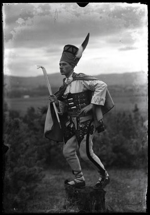 Portret Mieczysława Cholewy w planie pełnym, na rozmytym tle przyrody i górskiego pejzażu, w stroju podhalańskim, w wysokim nakryciu głowy z piórem i ciupagą w ręce. Układ ciała przedstawia jedną z figur tanecznych, w wykroku i z ręką na biodrze, co pozwala zademonstrować szczegóły stroju – szeroki nitowany pas i haftowane w parzenice spodnie.