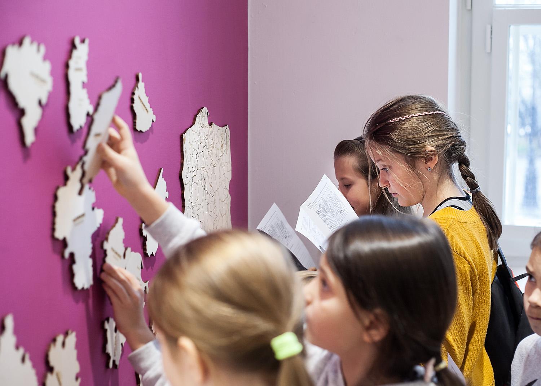 Zdjęcie kolorowe przedstawiające dzieci przyczepiające do ściany fragmenty układanki w kształcie mapy.