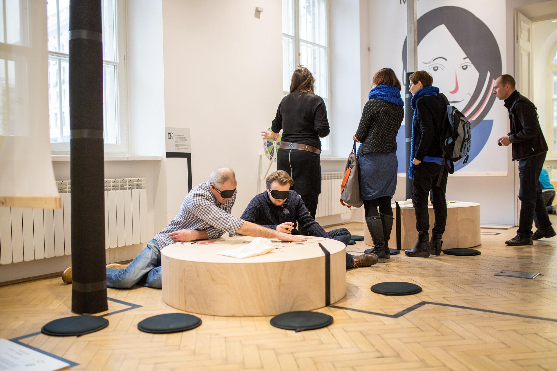 Fotografia kolorowa przedstawiająca wnętrze: drewniany parkiet, okna oraz cylindryczny, płaski kubik po środku. Przy kubiku siedzą dwie osoby z czarnymi przepaskami na oczach. Stojący obok ludzie przyglądają się obiektowi znajdującemu się obok okna.