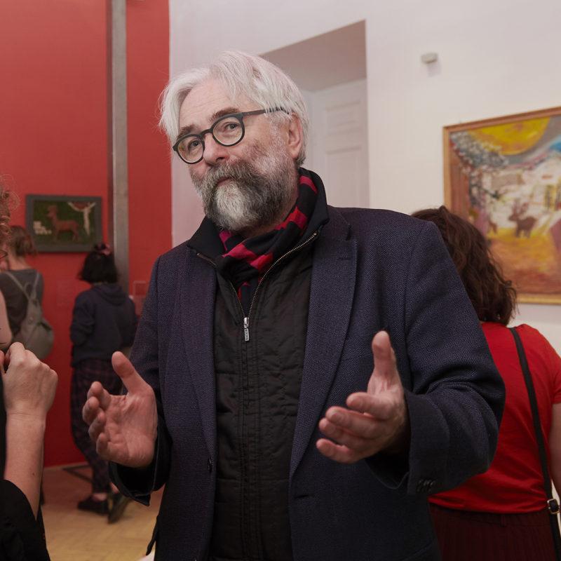 Zdjęcie kolorowe przedstawiające przemawiającego dyrektora Muzeum. W tle widoczny kolorowy obraz z jelonkiem.