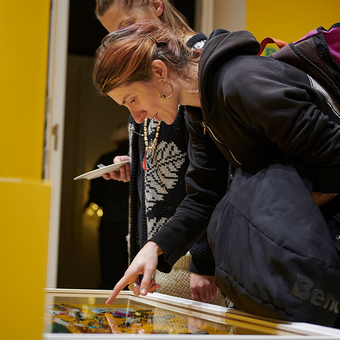 Zdjęcie kolorowe przedstawiające dwie kobiety nachylające się nad szklaną gablotą. Jedna wskazuje palcem na gablotę, druga trzyma w dłoni biały talerzyk.