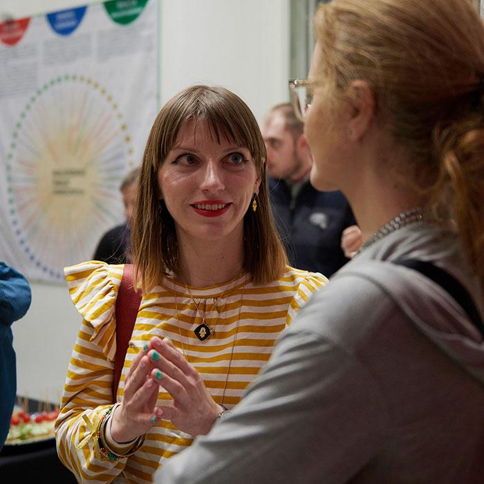 Zdjęcie kolorowe przedstawiające kuratorkę wystawy rozmawiające z kobietą. Kurratorka ubrana w bluzkę w biało-żółte paski.