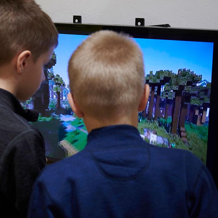Zdjęcie kolorowe przedstawiające dwóch chłopców przyglądających się ekranowi. Na ekranie widoczna gra Minecraft z odtworzoną wirtualną makietą Puszczy Białowieskiej.