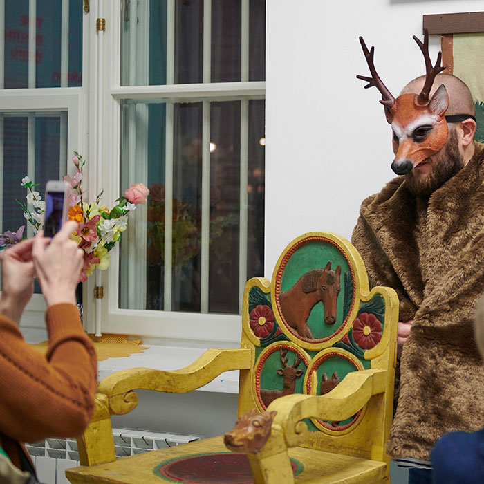 Zdjęcie kolorowe przedstawiające przebranego w futerko i maskę jelenia mężczynę, któremu zdjęcie robi telefonem kobieta. Mężczyzna stoi za żółtym, drewniamym, rzeźbionym fortelem, na którym widnieje wizerunek jelenia, konia, czerwonych kwiatów. W tle widoczne zakratowane okna.