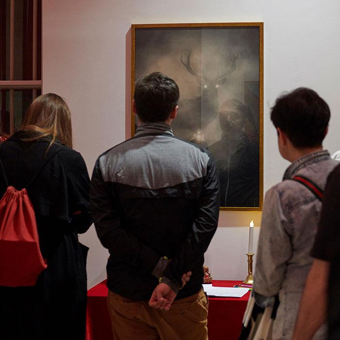 Zdjęcie kolorowe przedstawiające ludzi widzianych od tyłu, przyglądających się obrazowi na ścianie. Na obrazie okazały jeleń ze świecącymi oczami wyłaniający się z mgły.