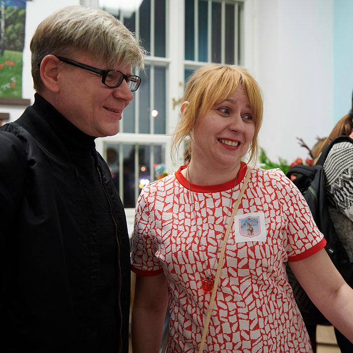 Zdjęcie kolorowe przedstawiające kobietę (realizatorka wystawy) i mężczyznę. Kobieta ubrana jest w biało-czerwoną sukienkę, na piersi ma przyklejoną naklejkę z wystawy. Mężczyzna stoi bokiem, ma okulary i ubrany jest na ciemno.