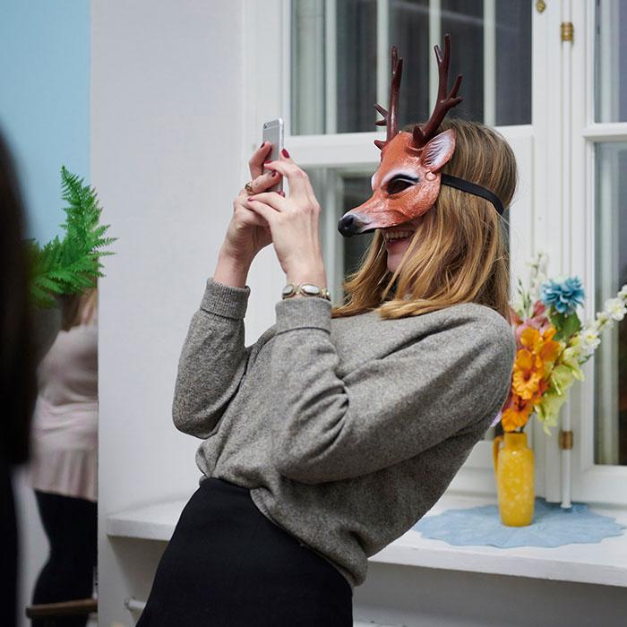 Zdjęcie kolorowe przedstawiające kobietę w masce lisa z rogami jelenia. Konieta robi sobie zdjęcie telefonem.