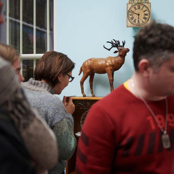 Zdjęcie kolorowe przedstawiające ludzi na wystawie. W tle widoczna drewniana figurka jelenia i stylowy, starodawny zegar.