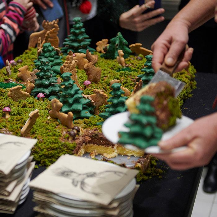 Fotografia kolorowa przedstawająca tort przypominający runo leśne. Widoczne cukrowe choinki, piernikowe łosie. Na pierwszym planie dłonie osoby nakładającej kawałki tortu na talerzyki.