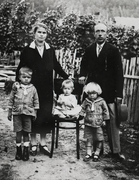Portret rodzinny. Matka, ojciej i trójka dzieci - najmłodsze siedzi na krześle ustawionym w centrum kadru. Pazują na tle płotu i roślinności.
