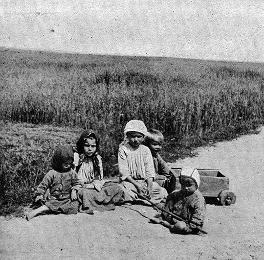 Wiejskie dzieci siedzące na drodze. Na głowach mają chusty i kapelusze co wzkazuje, że fotografia wykonana była w ciepły, letni dzień.