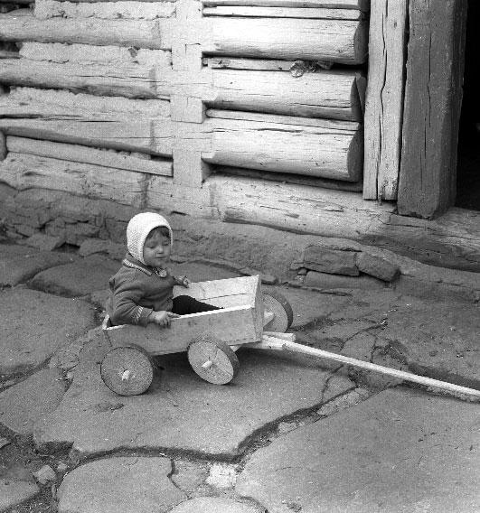 Dziecko wiejskie w drewanianym wózku-zabawce do ciągnięcia. W tle: drewaniana, wykoanna z bali, ściana budynku.