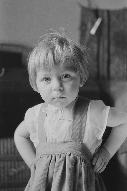 Dziewczynka w wieku okołu 2 lat. Ubrana w sukienkę, patrzący prosto w stronę obiektywu i podtrzymuje się za boczki.Zdjęcie czarno-białe.