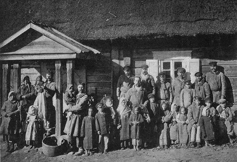 Grupa ludzi zgromadzona przed budynkiem. Dzieci i dorośli. Zdjęcie pamiatkowe, pozowane.