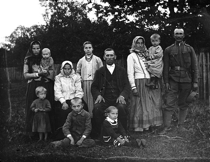 Rodzina pozująca do zdjęcia na tle płotu, roślinności. Ojciec siedzi na krześle w centralnej części kadru, wokół dzieci i kobiety, oraz mężczyna w stroju wojskowym. Zdjęcie czarno-białe.