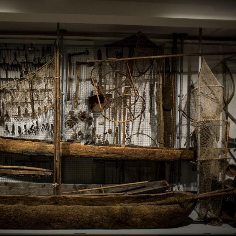 Na dole czółna drewniane dłubane oraz łódź, powieszone sieci oraz inny sprzęt rybacki.