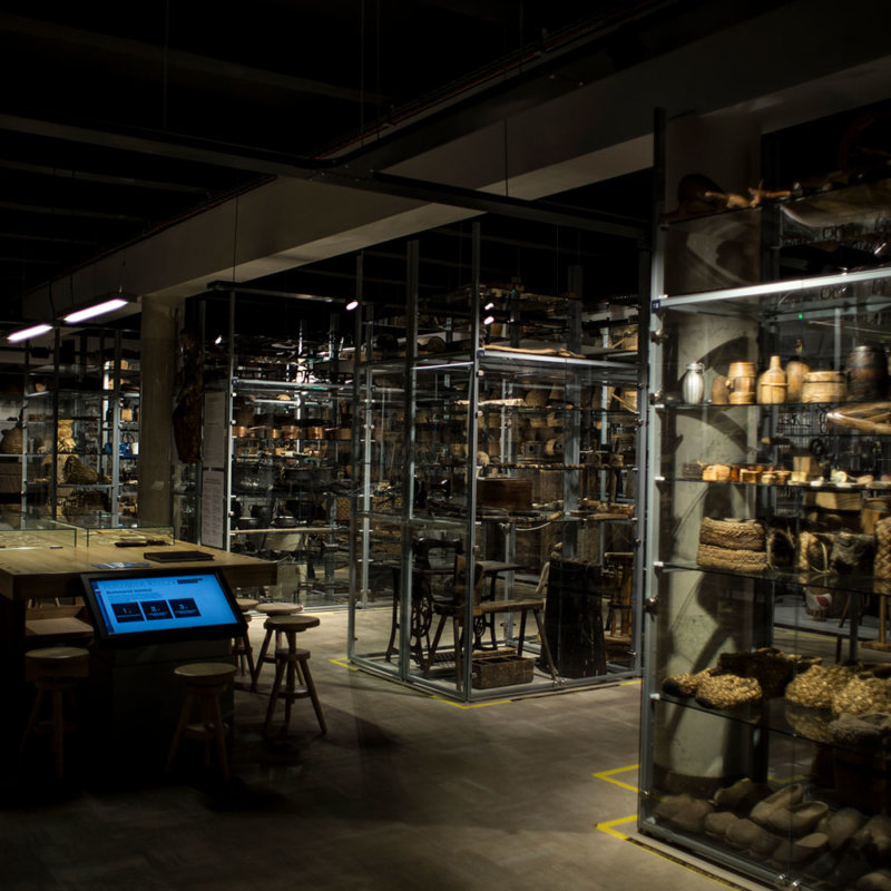 Fragment wystawy. Stół, stołki drewniane, metalowo-szklane wysokie gabloty z różnymi przedmiotami.