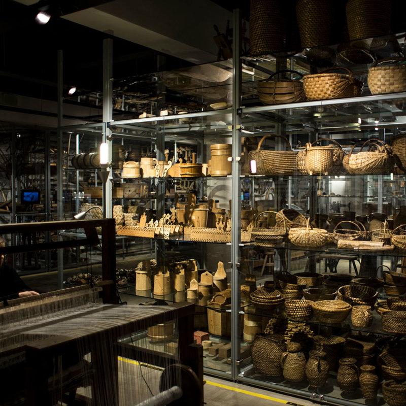 Na pierwszym planie warsztat tkacki do tkania. W gablocie kosze z różnych materiałów plecionkarskich oraz naczynia drewniane, np. solniczki.
