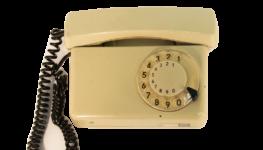 Zdjęcie kolorowe. Przedstawia dawny typ telefonu z tarczą do wybierania numerów i słuchawką na spiralnie skęconym kablu.