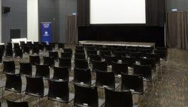 Zdjęcie kolorowe przedstawiające salę kinową z widocznym ekranem oraz rzędami czarnych, plastikowych krzesełek.