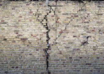 Na fotografii ceglana ściana w kolorach ziemi (ceglany, szary, zielonkawy, biały), z nieregularnym pionowym pęknięciem rozgałęziającym się ku górze.