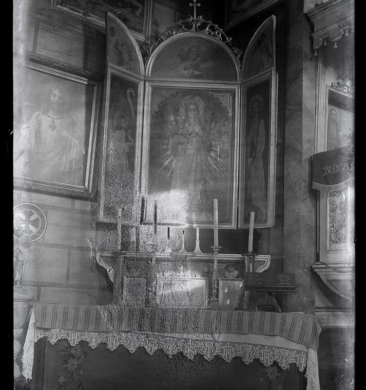 Tryptyk z centralnie umieszczonym obrazem Matki Bożej nad bocznym ołtarzem w kościele, na ścianach obok inne obrazy religijne.