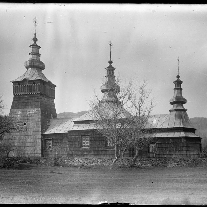 Cerkiew drewniana trójdzielna typu łemkowskiego, widok z boku. Cerkiew zwieńczona blaszanym namiotowym dachem, uformowanym w trzy kopuły, z najwyższą wieżą dzwonniczą nad przedsionkiem.