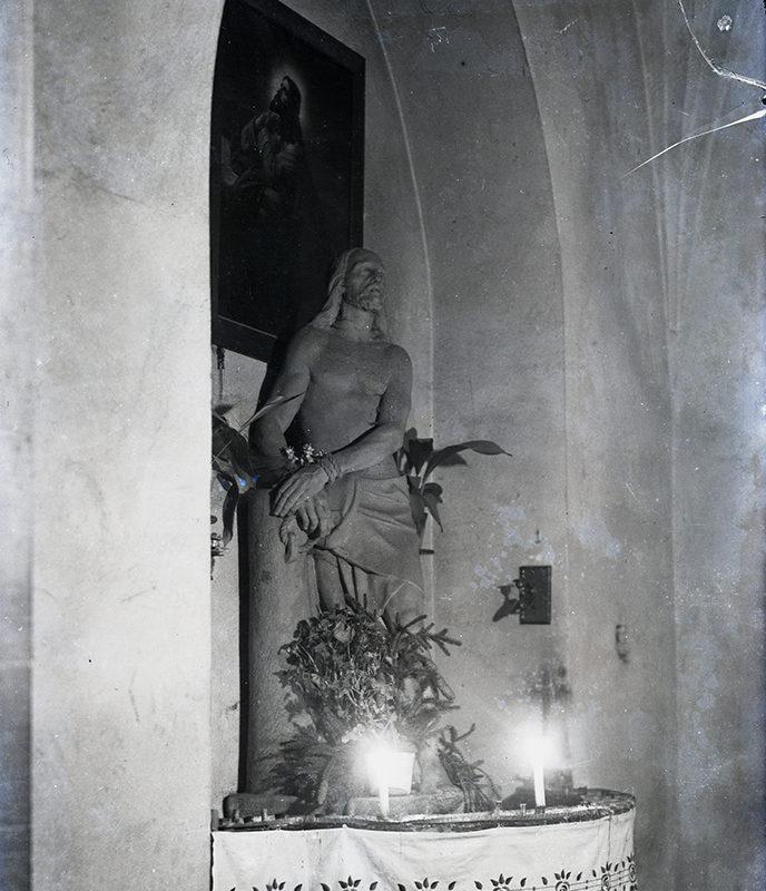 Scena pasyjna: figura Chrystusa ze spętanymi rękami stojącego przy słupie. Nad figurą na ścianie wnęki obraz Jezusa modlącego się w Ogrójcu.