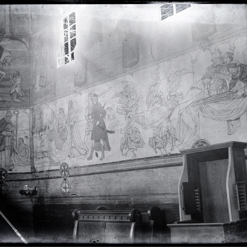 Wnętrze drewnianego kościoła z widokiem ściany bocznej ozdobionej polichromią przedstawiającą kolejne sceny z pogrzebu św. Stanisława, w tym ciało świętego niesione przez anioły. Widoczny także konfesjonał i drewniane ławy kościoła stojące przy ścianie nawy.