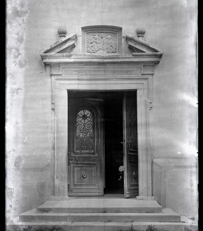 Barokowy portal kościoła św. Elżbiety, uchylone drewniane drzwi z ozdobnym okratowaniem, nad drzwiami fronton z płaskorzeźbą przedstawiającą św. Trójcę.