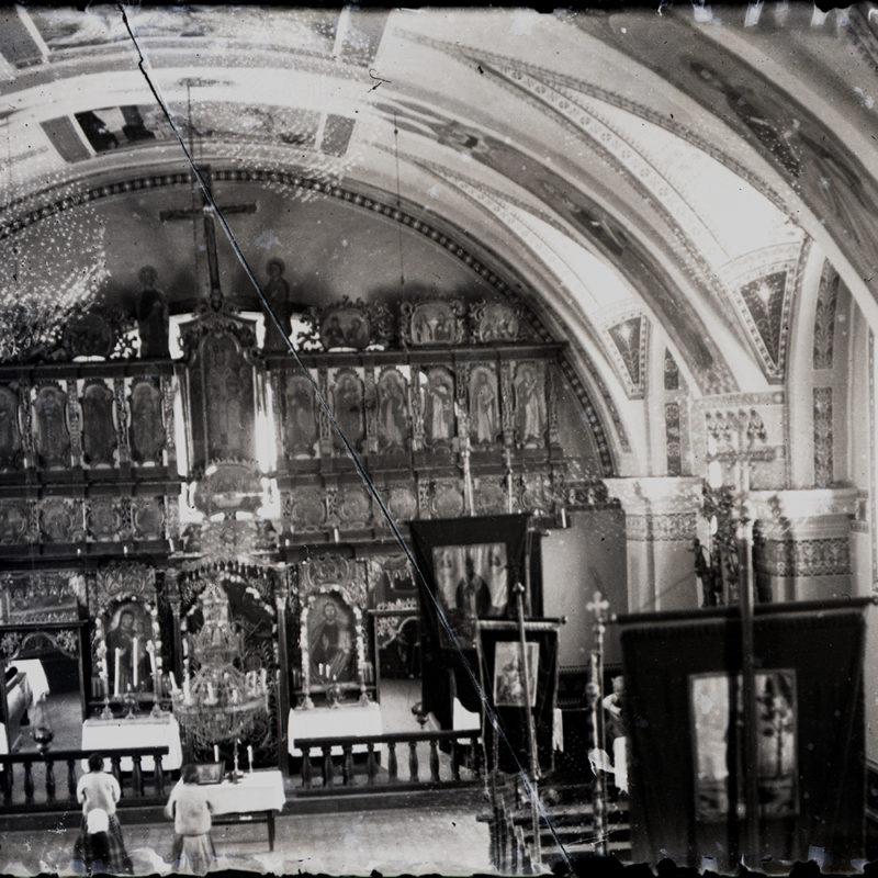 Widok z chóru cerkwi na ikonostas i fragment kolebkowego polichromowanego sklepienia. Widoczne feretrony i kilka modlących się osób.