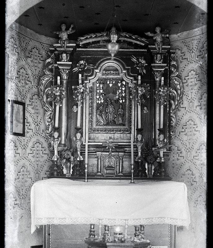 Barokowy ołtarz w półkolistej wnęce, z obrazem wotywnym przedstawiającym scenę Deesis (Chrystus na krzyżu, św. Jan i Matka Boża) oraz św. Trójcę, z florystyczną ornamentyką i puttami. Wnęka pokryta ornamentami. W dole ołtarza tabliczka z napisem: ofiara na budowę kaplicy.
