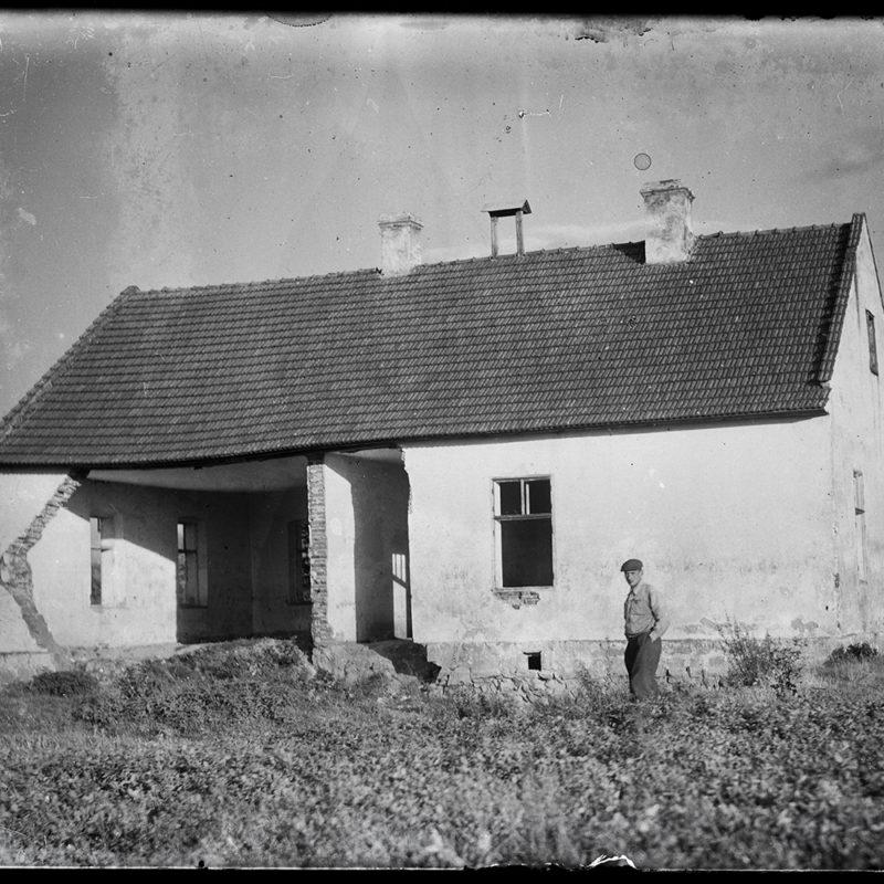 Murowana chałupa kryta dachem dwuspadowym, jednokondygnacyjna, w trakcie budowy, remontu lub rozbiórki, pozbawiona fragmentu ściany frontowej. Przed domem mężczyzna w kaszkiecie na głowie. Za chałupą widoczny fragment sadu.