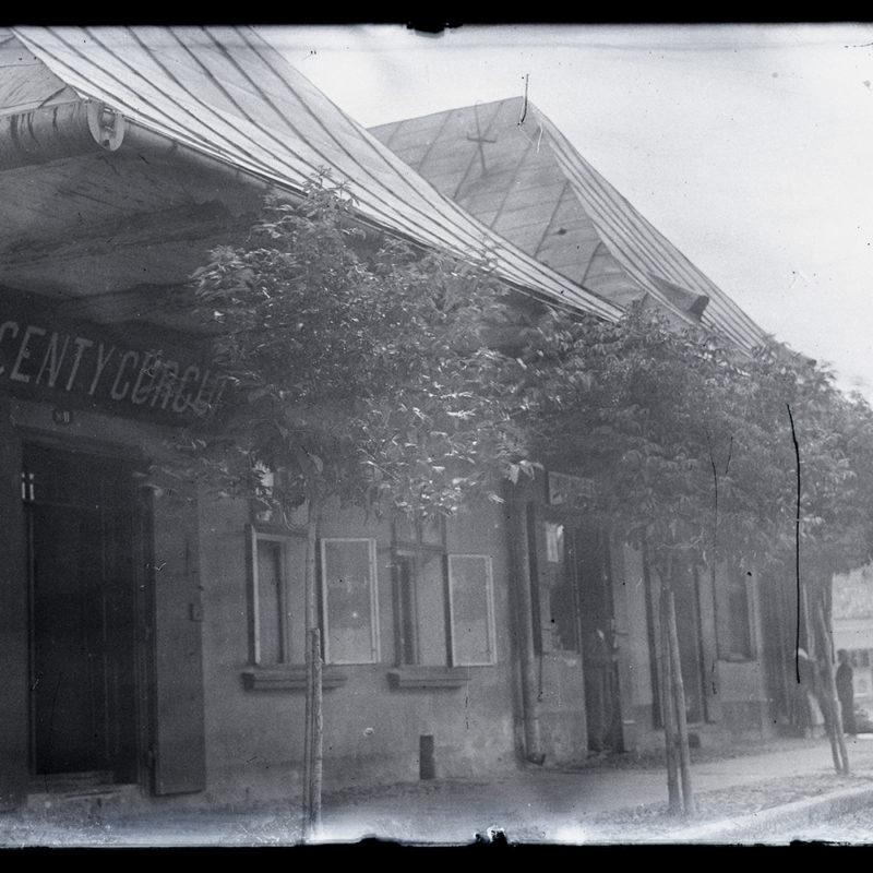 Fragment zabudowy małomiasteczkowej: widoczne dwa niskie domy na rogu ulicy, zwieńczone czterospadowymi dachami z blachy, z lokalami usługowymi i szyldami nad otwartymi drzwiami. Obok domów wzdłuż ulicy rosną młode drzewa.