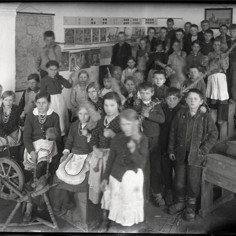 Grupa dzieci w klasie szkolnej, z akcesoriami służącymi do przędzenia (kołowrotki i przęślice). Część dzieci trzyma długi upleciony sznur, na podłodze leżą kłosy pozostałe po obróbce. Na ścianie szkolna gazetka i mapa przedwojennej Polski.