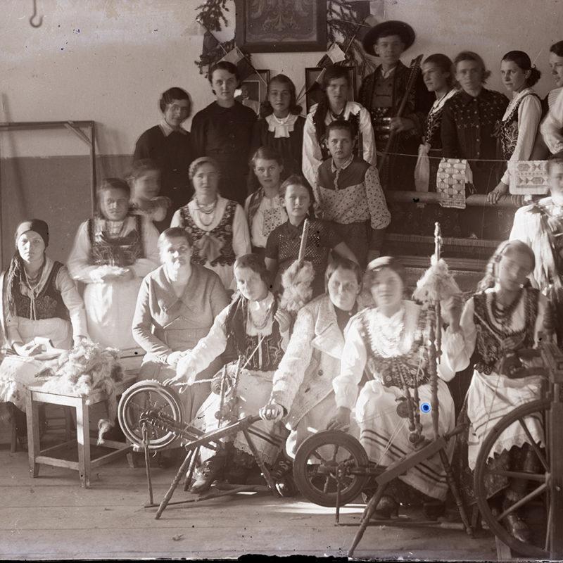 Grupa dzieci we wnętrzu szkolnym, ubranych w stroje sądeckie, pozująca wśród rekwizytów związanych z obróbką tkanin – trzech kołowrotków i warsztatu tkackiego. Kilkoro dzieci oraz nauczycielka ubrani są w codzienne stroje. Na ścianie fragment godła z dwiema biało-czerwonymi chorągiewkami, z boku piec kaflowy.