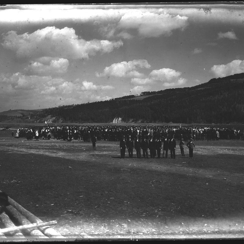 Panorama doliny i gór w tle, w głębi fotografii duża grupa świętujących górali, z mężczyznami stojącymi rzędem na pierwszym planie. Z boku fotografii ujęty przypadkowy mężczyzna, pochylający się nad belami ściętych drzew.