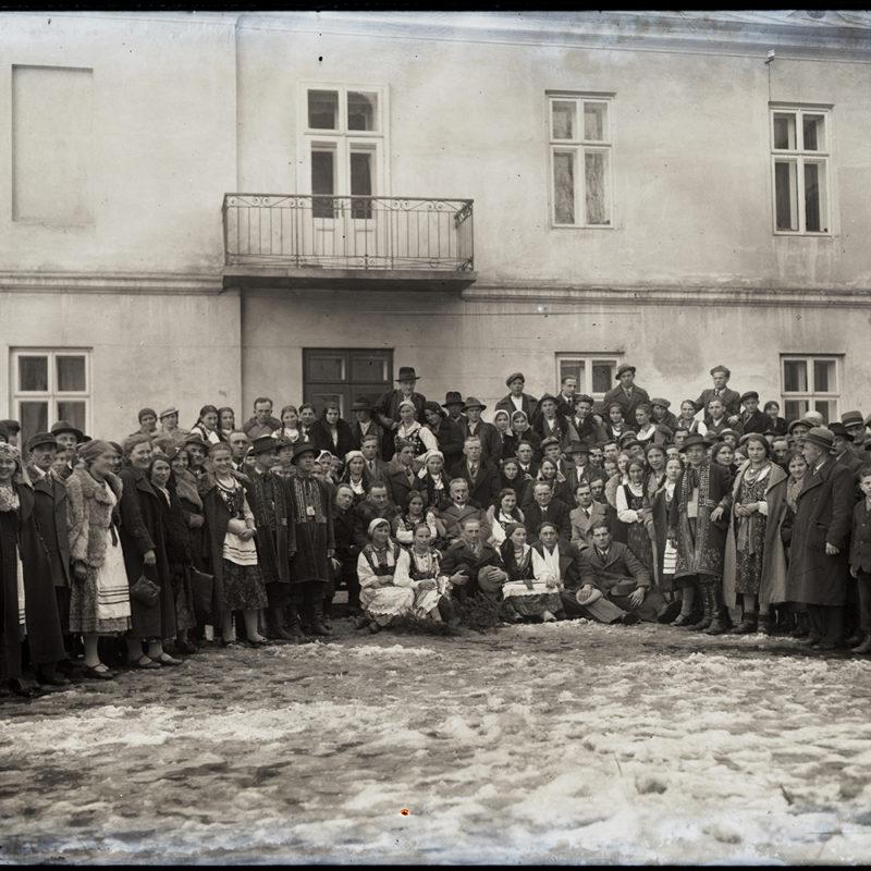 Duża grupa młodzieży w strojach sądeckich i podhalańskich oraz miejskich z lat 30. Przedstawione osoby pozują do zdjęcia stojąc w półkolu na tle kamienicy, niektórzy siedzą na gałązkach położonych na zalegającym na podwórzu śniegu.