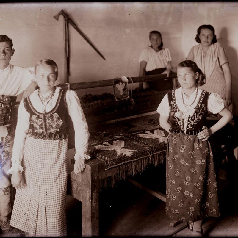 Grupa pięciu osób, czterech kobiet i jednego mężczyzny, upozowana przy krosnach tkackich z tkaniną w orły. Osoby na pierwszym planie noszą stroje góralskie, dwie pozostałe na planie dalszym przedstawione są mniej wyraźnie i mają na sobie strój codzienny.