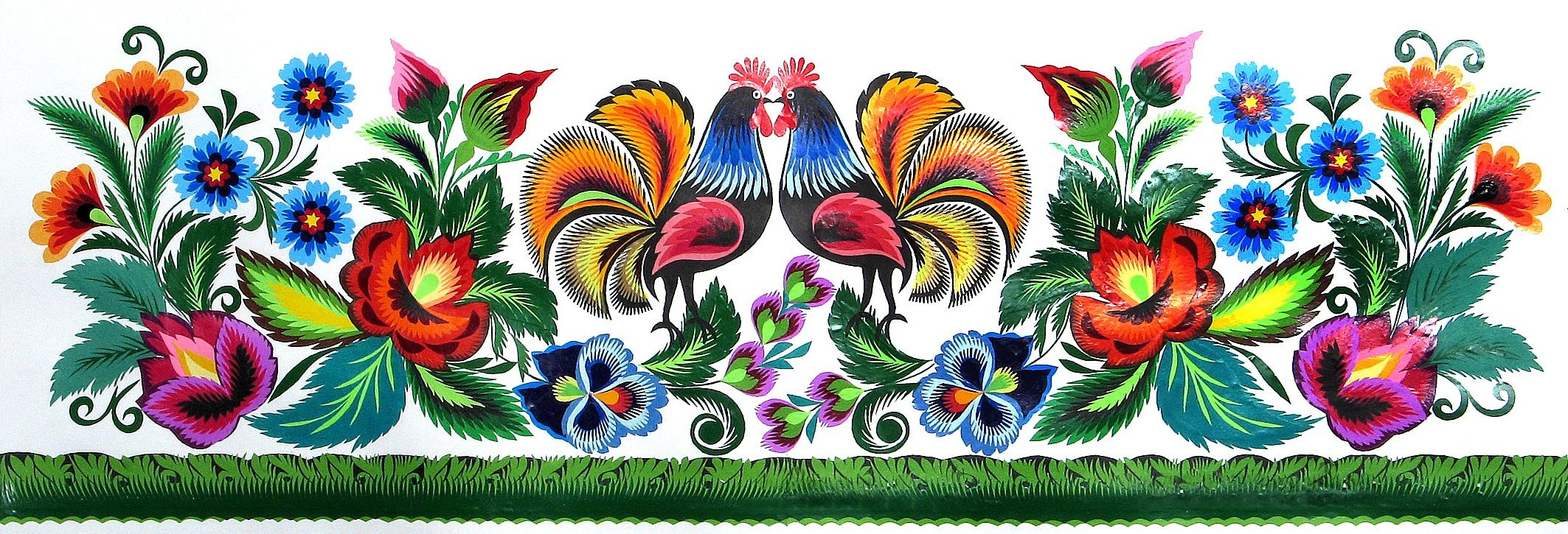 Szeroka wycinanka z kolekcji muzeum przedstawiająca w centrum dwa kolorowe koguty koguty, u dołu wycinankowy trawnik. Wycinanka przedstawia też dużo kolorowych kwiatów ponad trawnikiem, które okalają również koguty. Całość żywa i z wieloma detalami.