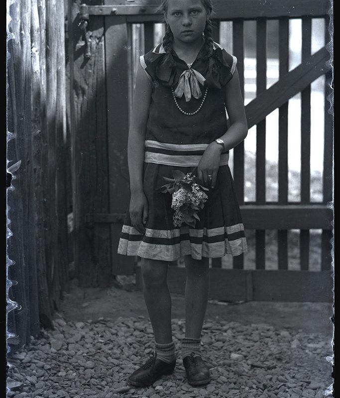 Portret dziewczynki w ujęciu frontalnym, z warkoczami. Ubrana jest w ciemną sukienkę bez rękawów, z jasnymi pasami w części dolnej, oraz czarne pantofle. W lewej dłoni nieco uniesionej ku górze trzyma bukiet z kwiatów bzu. Stoi na tle drewnianej furtki.
