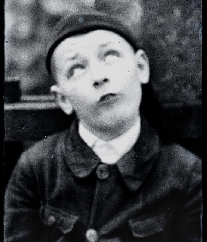 Portret chłopca, w popiersiu, z oczami wzniesionymi ku górze. Ubrany jest w czarną bluzę zapinaną na guziki, z naszytymi dużymi kieszonkami po bokach.