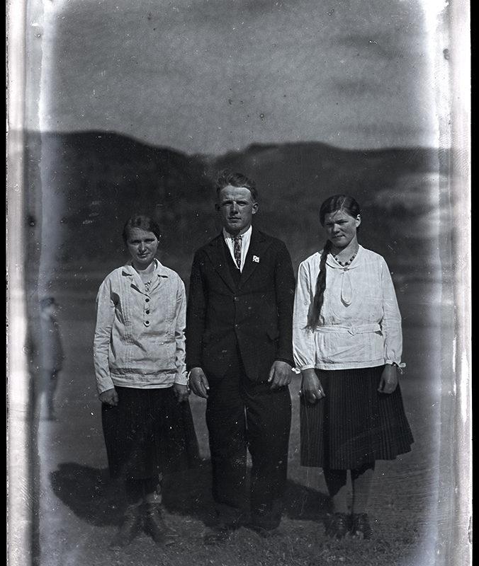 Troje młodych ludzi stojących na tle wzniesień górskich, pośrodku mężczyzna w czarnym garniturze, z jego prawej i lewej strony kobiety ubrane w ciemne spódnice i jasne bluzki.