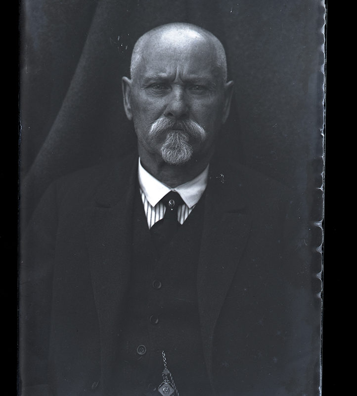 Portret starszego mężczyzny na tle kotary, w ujęciu frontalnym, do pasa. Ubrany jest w rozpiętą czarną marynarkę, pod nią nosi ciemną kamizelkę zapinaną na małe guziki oraz koszulę z białym kołnierzykiem i ciemny krawat.