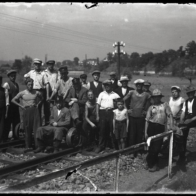 Duża grupa mężczyzn ubranych w robocze stroje, stojących na torach. Pośrodku drezyna. W tle rozległa dolina z zabudowaniami na stokach.