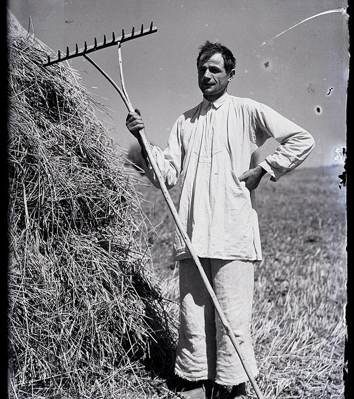 Stojący na polu mężczyzna ubrany w biały, płócienny strój: szerokie spodnie i długą koszulę marszczoną u góry. W prawej ręce trzyma grabie wsparte o ziemię. Z lewej strony widoczny fragment stogu siana.