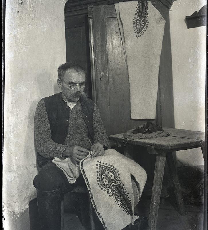 Mężczyzna ukazany we wnętrzu pracowni krawieckiej podczas pracy - ręcznego szycia jasnej sukmany zdobionej haftem. Z prawej strony drewniany stołek, za nim szafa z zawieszonymi na drzwiach jasnymi spodniami zdobionymi parzenicą.