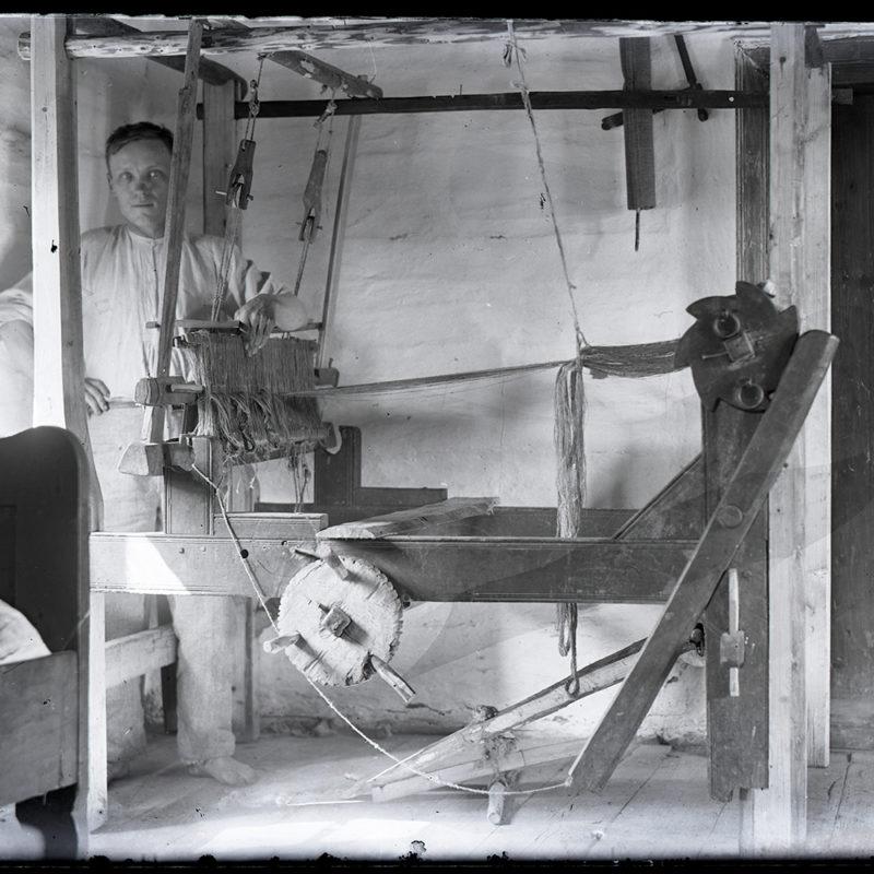 Warsztat tkacki w rogu mieszkania, za nim, z lewej strony stoi mężczyzna ubrany w biały płócienny strój (koszulę i spodnie). Z lewej strony widoczny fragment łóżka, z prawe fragment drzwi.