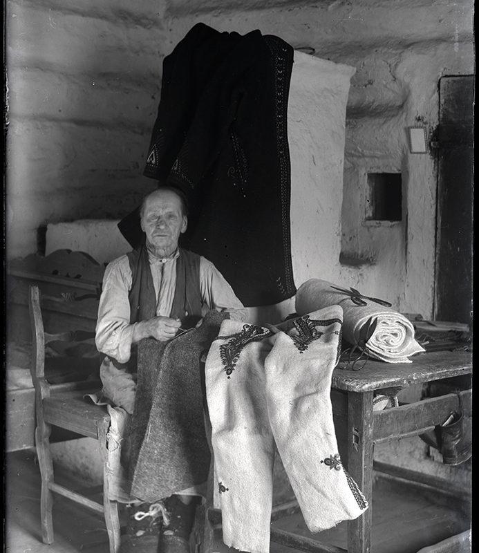 Mężczyzna w pracowni krawieckiej, szyjący stroje góralskie. Z prawej strony, na stole leżą jasne, zdobione geometrycznym haftem spodnie i bela jasnego płótna oraz nożyce. W tle piec okryty ciemnym płaszczem.